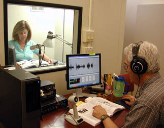 A volunteer reader and director work together to record a book.